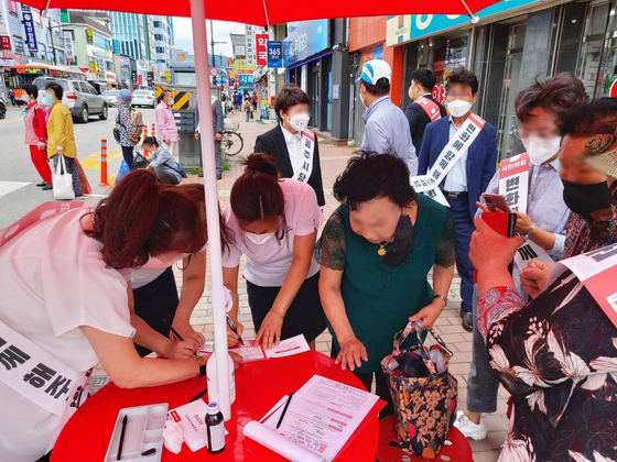 In this photo provided by Rep. Chung JIn-suk of the People Power Party on Wednesday, residents of Gongju, South Chungcheong, sign up for membership in the conservative party at a street booth.  [YONHAP]