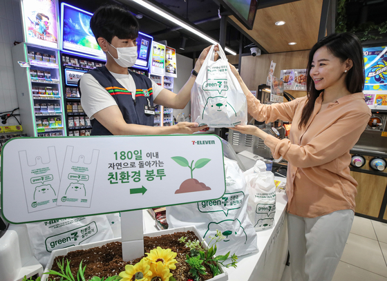 Models promote 7-Eleven's eco-friendly plastic bags on Wednesday at the convenience store's Yongsan branch in central Seoul. According to 7-Eleven, its plastic bags only take 180 days to decompose in landfills. They will be used in all of its branches across the country starting in mid-July and will cost 100 won (9 cents). 7-Eleven uses some 110 million plastic bags per year. Shifting to the eco-friendly version will reduce carbon emissions by 4,620 tons, according to the convenience store chain. [YONHAP]