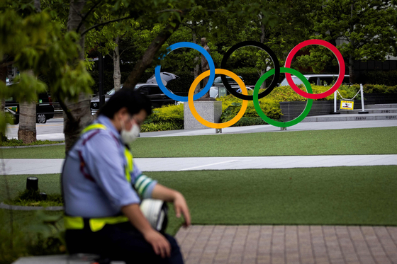 A security guard takes a break in front of the Olympic rings in Tokyo on June 3, 2021.  [AFP]