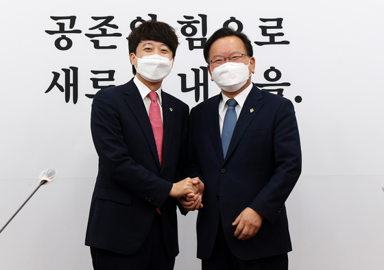 People Power Party Chairman Lee Jun-seok, left, takes a photo with Prime Minister Kim Boo-kyum, who pays a visit to the National Assembly to congratulate him for winning the leadership race.  [NEWS1]