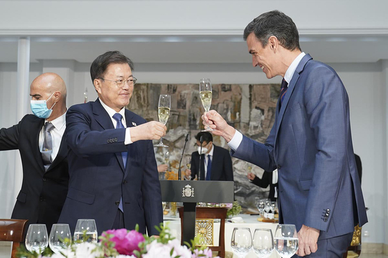 President Moon Jae-in, left, and Spanish Prime Minister Pedro Sanchez, right, toast each other at the Prime Minister's Palace in Madrid on Wednesday.  [BLUE HOUSE]