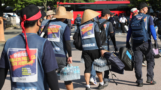 Deliverymen end a two-day sit-in protest in Yeouido, western Seoul, on Wednesday, after coming to an agreement with the logistics companies on improving working conditions.