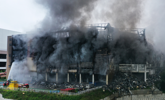 Coupang's Deokpyeong Logistics Center in Icheon, Gyeonggi, continues to burn on Friday. The fire, which broke out Thursday morning, continued through Friday and could take days to fully extinguish. [YONHAP]