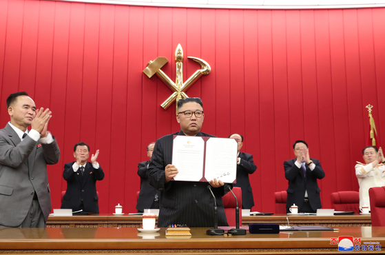 North Korean leader Kim Jong-un holds up a document signed by him to applause from participants in the third plenary session of the eighth Central Committee of the North's ruling Workers' Party Thursday, reported its official Korean Central News Agency Friday. The document is thought to be a special order signed off by Kim during the meeting which could address issues like food shortage. [YONHAP]