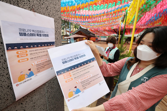 An employee poses with a poster about promotional event at Jogye Temple in Jongno District, central Seoul on June 1. Starting this month, vaccinated people or those who received their first jab will be offered to 20,000 won discounts on all temple stay programs in 135 temples across the country. [NEWS1]