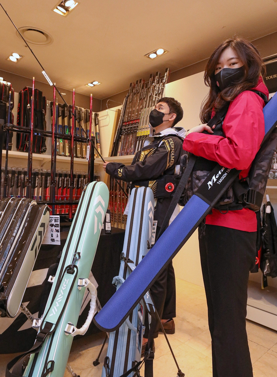 Employees show off fishing gear at a Hyundai Department Store branch in Apgujeong, southern Seoul, on Monday. The store will hold a ″Premium Fishing Fair″ through Sunday in partnership with fishing brand Daiwa. [YONHAP]