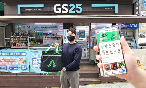 A model promotes GS25's delivery app Woodel on Monday. The company said it launched a mobile app for its delivery service for convenience store GS25 and GS Supermarket, which was previously only available either through Yogiyo app or KakaoTalk. [YONHAP]