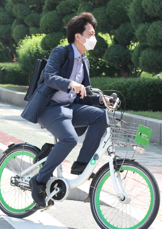 New opposition leader Lee Jun-seok wears a backpack and rides a bike to report to work in the National Assembly on June 13. [OH JONG-TAEK]