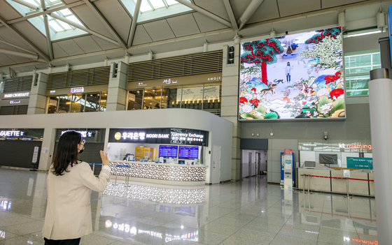 A visitor interfaces with an interactive media art installation at Incheon International Airport's Terminal 1 on Monday. The airport said the installation uses cutting-edge information and communications technology. [YONHAP]