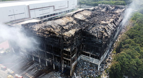 Smokes continues to rise Sunday from Coupang's Deokpyeong Logistics Center in Icheon, Gyeonggi, which was destroyed by a fire that started Thursday morning. [NEWS1]