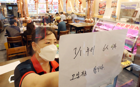 An employee puts up a notice on the wall of a restaurant in Myeong-dong, central Seoul, on Monday, to inform customers of eased social distancing guidelines that will allow private gatherings of up to six people from July in the greater Seoul area. [YONHAP]