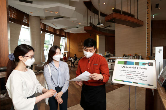 An employee of The Courtyard by Marriott Seoul Times Square talks to customers about a promotional event at its buffet restaurant in Yeongdeungpo District, western Seoul. The hotel offers breakfast buffet at 100 won ($0.09) for customers vaccinated, as well as their companions, if they are staying at the hotel. [JANG JIN-YOUNG]