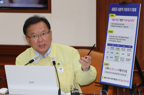 Prime Minister Kim Boo-kyum explains the government's new social distancing scheme during a Covid-19 response meeting at the government complex in Seoul on Sunday. The new rules center on allowing gatherings of more people and lifting regulations for businesses, and will go into effect July 1. [YONHAP]