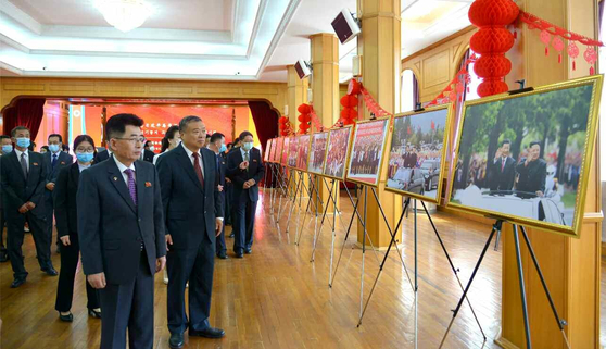 North Korean officials and Chinese Ambassador to North Korea Li Jinjun view a photo exhibition at the Chinese Embassy in Pyongyang to mark the second anniversary of Chinese President Xi Jinping's first state visit to the country in 2019 for a summit with leader Kim Jong-un in a photograph carried by the North's official Rodong Sinmun. [RODONG SINMUN]