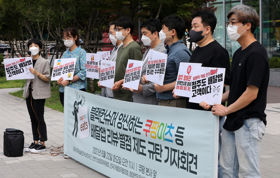 Civic groups and union members hold a press conference in front of Coupang's headquarters in Songpa District, southern Seoul, on Tuesday, arguing against the review and rating system on the delivery app that results in abuse of power against restaurant owners. [NEWS1]