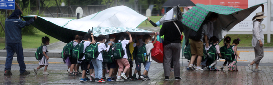 Kindergartners take refuge under their picnic mats during sudden showers on Tuesday afternoon at a park in Seoul. [YONHAP]