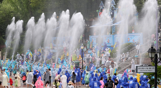 """At the amusement park Everland in Yongin, Gyeonggi, on Tuesday, people enjoy getting doused with water cannons at the water festival """"Shooting Water Fun."""" [YONHAP]"""