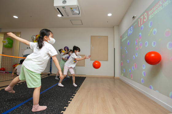 Children participate in an indoor field day at the Yongsan District Office in Seoul on Tuesday. KT said it is working with four institutions within Yongsan on a metaverse field trip using its KT Real Cube system. Without having to wear special equipment, children can take part in the online field trip, which uses motion sensors so they can play games with other kindergarten children via virtual reality and augmented reality systems. [KT]