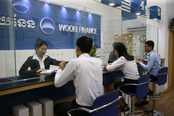 An employee advises a customer at WB Finance's branch in Cambodia. [WOORI BANK]