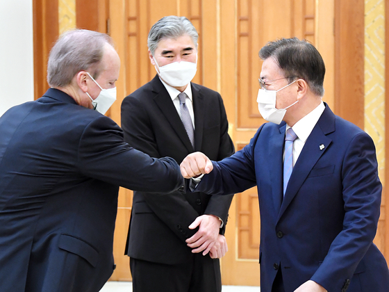 President Moon Jae-in, right, bumps elbows with Rob Rapson, acting U.S. ambassador to South Korea, left, with U.S. nuclear envoy Sung Kim, center, watching during a courtesy call to the Blue House in central Seoul Tuesday. [JOINT PRESS CORPS]