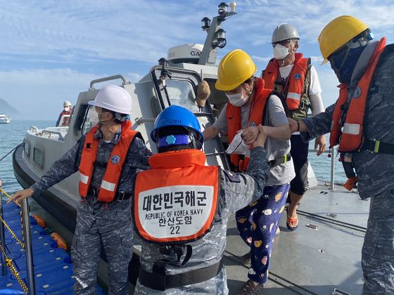 Helped by sailors, a resident from a remote island arrives on Korea's first military training vessel, Hansando, off Jin Island, South Jeolla, on Tuesday. The Navy has conducted an operation to help residents from remote islands, devoid of medical facilities, receive Covid-19 vaccine shots at a mass vaccination center installed on the ship. [YONHAP]