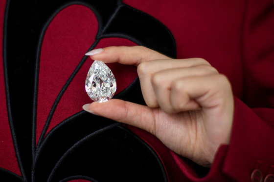 An employee of Sotheby's poses with a rare pear-shaped 100-carat diamond at Sotheby's in New York on Monday. [REUTERS/YONHAP]