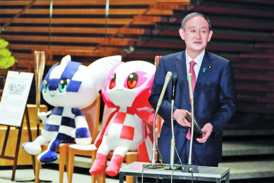 Japanese Prime Minister Yoshihide Suga, next to the mascots of Tokyo 2020 Olympic and Paralympic Games, speaks to media after announcing that Tokyo, Kyoto and Okinawa will receive pre-emergency status under a new prevention law during a government task force meeting at the Prime Minister's Office in Tokyo on April 9, 2021. [YONHAP]