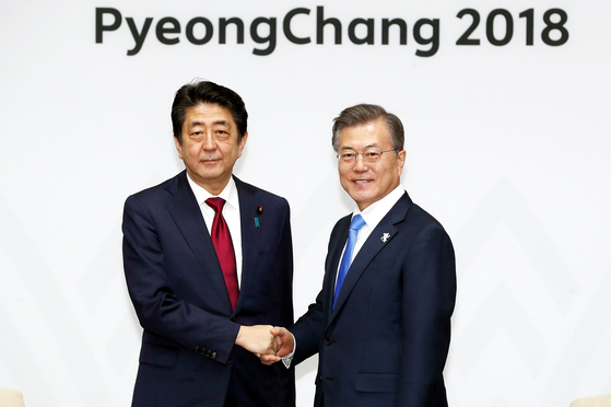 In this file photo, President Moon Jae-in, right, and Japanese Prime Minister Shinzo Abe stand for a photo before their summit in Yongpyeong, Gangwon Province, on the sidelines of PyeongChang Winter Olympic Games in 2018.  [Presidential Press Corps]
