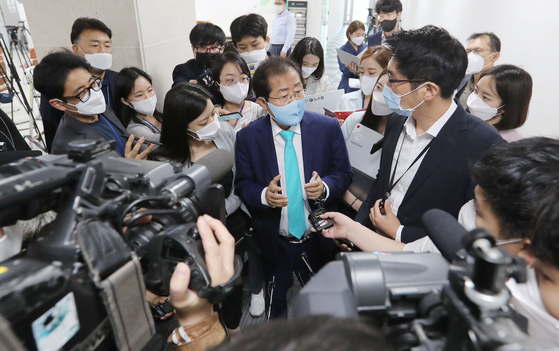 Rep. Hong Joon-pyo, center, talks to reporters after a press conference at the National Assembly on Wednesday. Earlier in the morning, the People Power Party's Supreme Council approved Hong's return to the party after 15 months. [YONHAP]