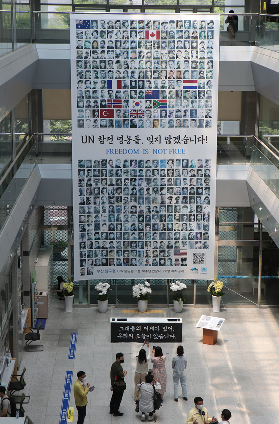 The banner exhibiting the portraits of 388 Korean War veterans is placed at the Nam District Office in Busan on Thursday to commemorate the 71st anniversary of the outbreak of the Korean War and the 70th anniversary of the foundation of the UN Memorial Cemetery in Korea in Busan. [SONG BONG-GEUN]