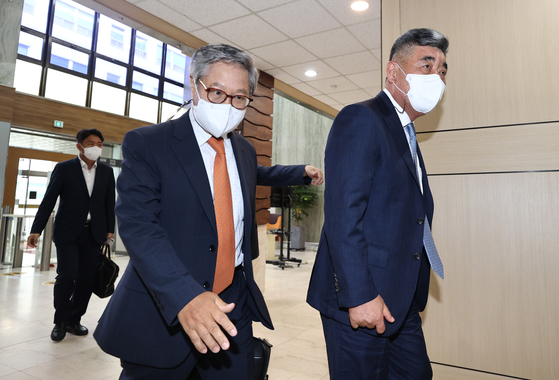 Sung Jung chairman Hyoung Nam-sun, right, and Eastar Jet representative Jeong Jae-sup walk into Seoul Bankruptcy Court in Seocho District, southern Seoul, on Thursday to sign a deal to sell the budget carrier to Sung Jung. [YONHAP]