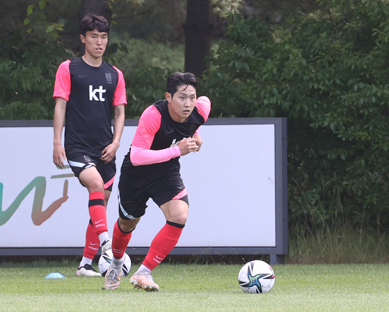 Lee Kang-in, right, runs with the ball at the National Football Center in Paju, Gyeonggi, on Wednesday. Lee and the rest of the U-23 squad have gathered at the center for a final training session before the squad for the 2020 Tokyo Olympics is announced next week. [YONHAP]