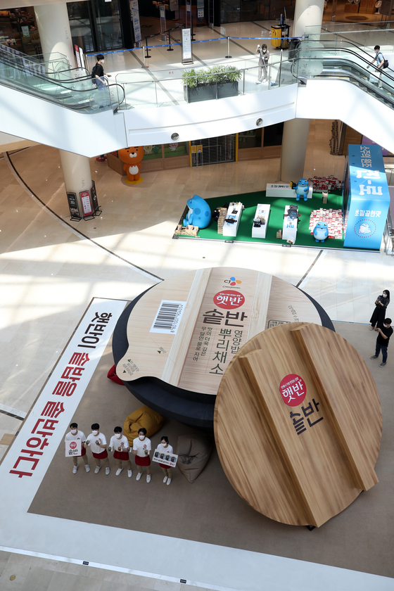 Models promote CJ CheilJedang's new instant rice product on Sunday before a mega-sized installation in the shape of a gamasot, a traditional pot used for rice cooking, at the Times Square in Yeongdeungpo, western Seoul. [YONHAP]