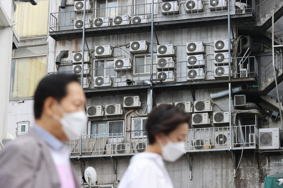 Air conditioners on the side of a building in Jung District, central Seoul on June 21. On the news of the government freezing electric bills again, Korea Electric Power Corporation shares tumbled 6.88 percent on June 21 compared to the previous session. [YONHAP]