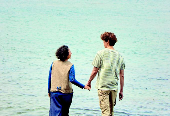 """Actor Goh Doo-shim holds hands with actor Ji Hyun-woo in a scene from """"Everglow,"""" which will hit local theaters on June 30. [MYUNG FILM]"""
