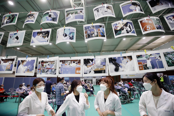 Health workers look at photos hung inside the vaccination center in Gwangju on Monday, after the district office installed a photo exhibition to thank the medical staff for their hard work during the Covid-19 pandemic. [NEWS1]