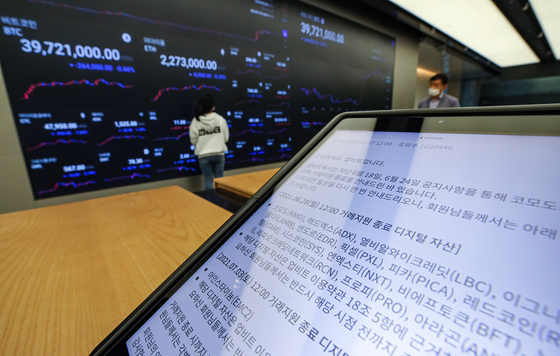 A tablet PC at Upbit lounge in Gangnam District, southern Seoul, on Monday displays a notice of the exchange ending trading of 23 coins from noon that day. While the exchange announced plans to delist 24 coins on June 18, trading of one more coin will end on July 3. [YONHAP]