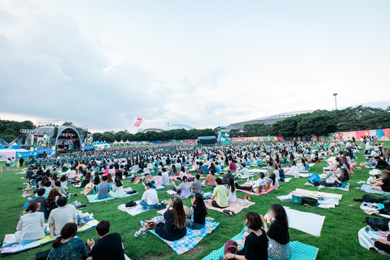 Festivalgoers at The Beautiful Mint Life 2021 music festival watch performances on picnic mats Saturday at Olympic Park in southern Seoul. The Beautiful Mint Life 2021 is Korea's first large-scale outdoor music festival to be held in a year and eight months since the Covid-19 pandemic broke out early last year. All visitors must use a self-testing kit to help ensure they do not have the virus. [NEWS1]