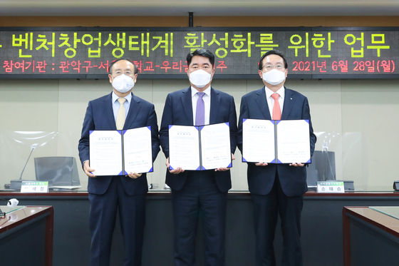 From left, Seoul National University President Oh Se-jung, head of Gwanak District Office Park Jun-hee, and Woori Financial Group Chairman Son Tae-seung pose for a photo after inking a memorandum of understanding on Monday at Gwanak District Office in southern Seoul. [WOORI FINANCIAL GROUP]