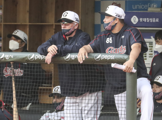 Lotte Giants manager Larry Sutton, left, watches a game against the NC Dinos at Sajik Baseball Stadium in Busan on June 22. [YONHAP]