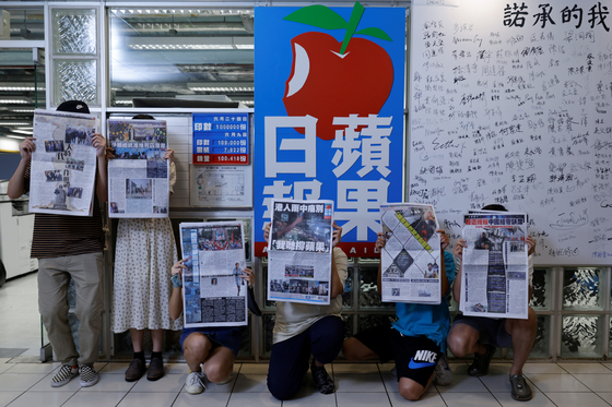 Staff members of Apple Daily and its publisher Next Digital pose with the final edition of the newspaper at its headquarters in Hong Kong on June 24.