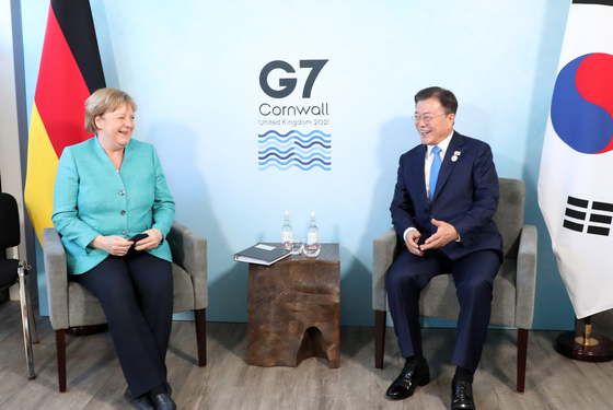 Korean President Moon Jae-in, right, discusses vaccine cooperation with German Chancellor Angela Merkel during a bilateral meeting on the sidelines of the G7 summit in Cornwall, England, on June 12. Moon also held a series of bilateral meetings with the leaders of Britain, Australia, France and the European Union. [YONHAP]