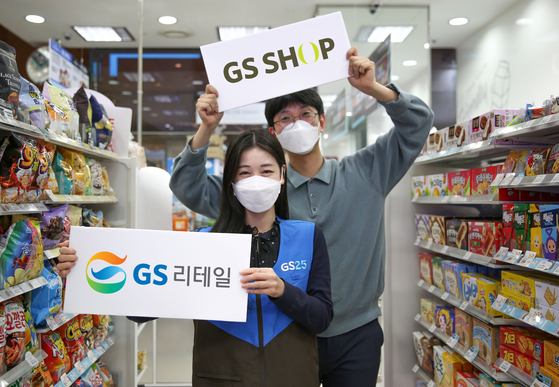 Models hold placards with the logos of GS Retail and GS Home Shopping. [GS RETAIL]