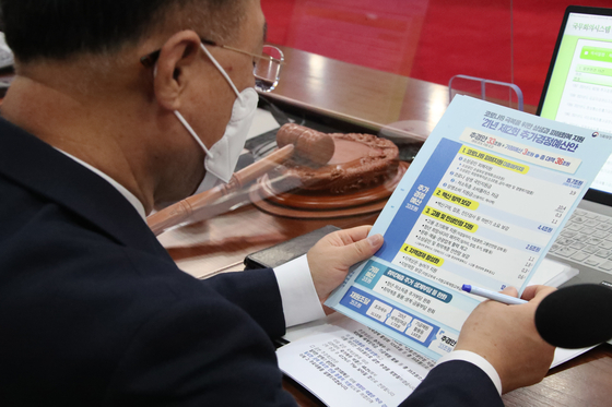 Finance Minsiter Hong Nam-ki consults data on the latest supplementary budget while attending a cabinet meeting at the government complex in Seoul on Thursday. [YONHAP]