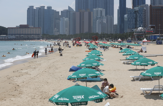 Parasols are set up on Haeundae Beach in Busan Thursday as the beach began allowing people to swim in the water from July 1. [NEWS1]