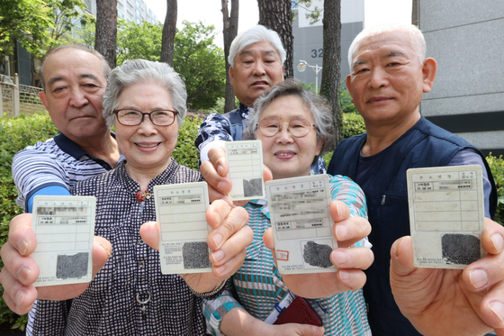 Vaccinated elderly people, sporting maskless faces, show their ID cards with inoculation stickers in Seoul on Monday, as the country began to issue the stickers to vaccinated people for mask-free activities. The vaccination certification is also available in a paper document or digitally on the COOV app. [YONHAP]