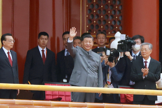Chinese President Xi Jinping, center, waves next to Premier Li Keqiang and former president Hu Jintao at the end of the event marking the 100th founding anniversary of the Communist Party of China, on Tiananmen Square in Beijing on Thursday. [REUTERS/YONHAP]
