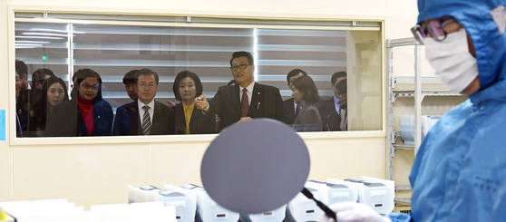 President Moon Jae-in, center, watches a demonstration on etching semiconductors using hydrogen fluoride at an MEMC plant in Cheonan, South Chungcheong, in November 2019. [YONHAP]