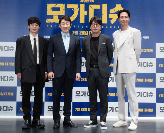 """Leads in the highly anticipated """"Escape from Mogadishu"""" — from left, actors Koo Kyo-hwan, Huh Joon-ho, Kim Yoon-seok and Zo In-sung — pose at an online press event Thursday. [LOTTE ENTERTAINMENT]"""