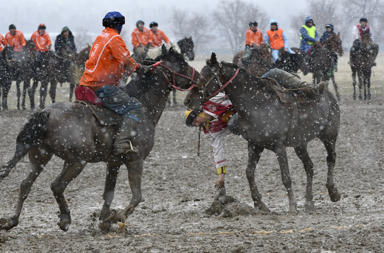 Riders compete during a kok boru, also called ulak tartysh, a traditional game in which players on horseback maneuver with a goat's carcass and score by putting it into the opponents' goal outside Sokuluk village, 12,5 miles west of Bishkek, Kyrgyzstan on March 30. [AP PHOTO/VLADIMIR VORONIN]